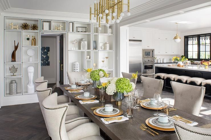 Jonathan Adler Meurice Rectangular Chandelier Lights A Walnut Stained Dining Table Surrounded By Cream Upholstered Wingback Chairs Placed On