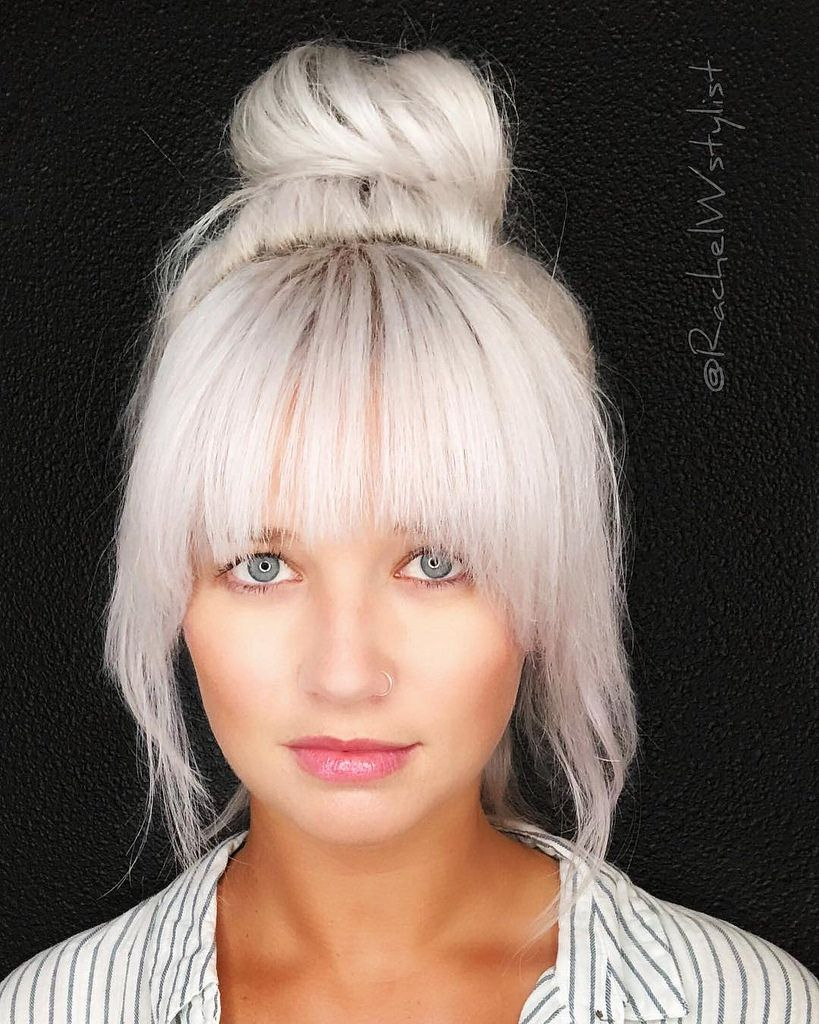 Large Messy Top Bun With Full Face Framing Fringe And Platinum Blonde Hair Color Blonde Hair With Bangs Platinum Blonde Hair Blonde Hair With Fringe