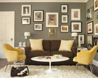 Grey walls brown couch black frames with pop of color and lots