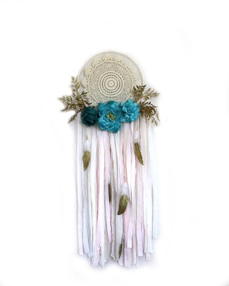 """Whimsical turquoise, gold and cream dreamcatcher. Metal hoop is wrapped in coordinating ribbon with crochet doily in center, attached with metallic thread. Strands consist of frabric, lace, pompom trim, and gold glitter feathers. 3 roses and leaf picks adorn bottom of hoop. 12""""diameter x 50""""l"""