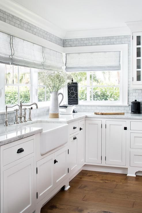 Contemporary cottage styled with square oil rubbed bronze knobs on white shaker cabinets finished with white and gray quartz countertops. #whiteshakercabinets