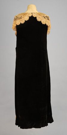 """SADIE NEMSER VELVET and LACE TEA GOWN, LATE 1920's. Sleeveless black velvet A-line having large bib front draping the shoulder and forming back collar, and two large front skirt gores pieced in various laces including Irish crochet, tape and needlepoint laces, side closure. Label """"Nemser Original Model"""". Back"""