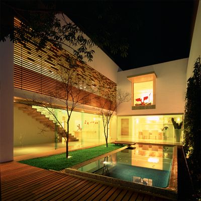 wooden decking and greenery around a pool, glass walls help the ...