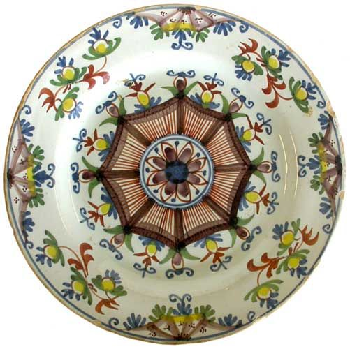 An 'Ann Gomm' delft plate of traditional form with spider's web decoration and floral rosette, bordered by flower buds, painted in blue, manganese, red, green and yellow on a pale bluish glaze, probably London, 1790, 9in diameter.