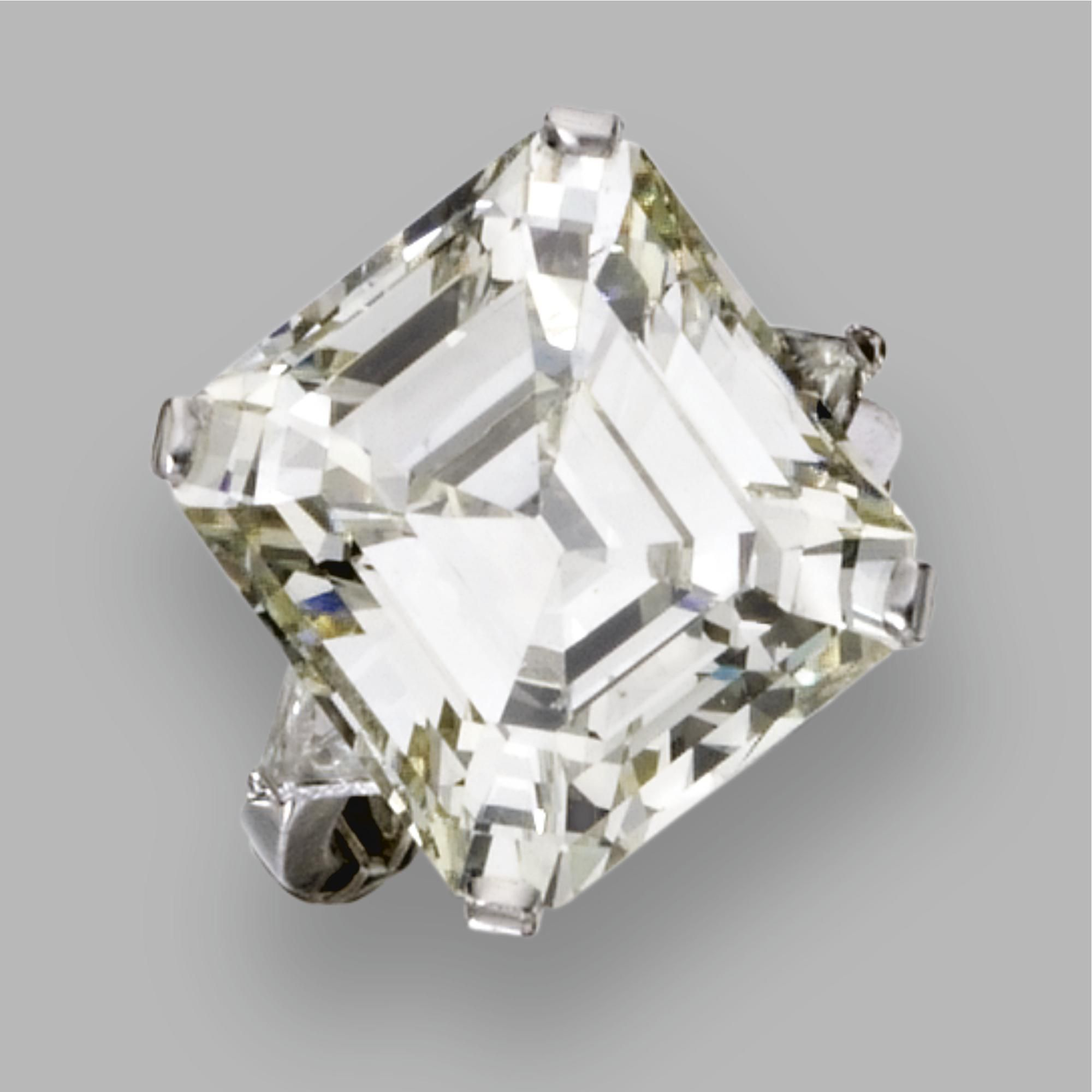 DIAMOND RING The emerald-cut diamond weighing 23.76 carats, flanked by 2 triangular-shaped diamonds weighing approximately .90 carat, mounted in platinum.