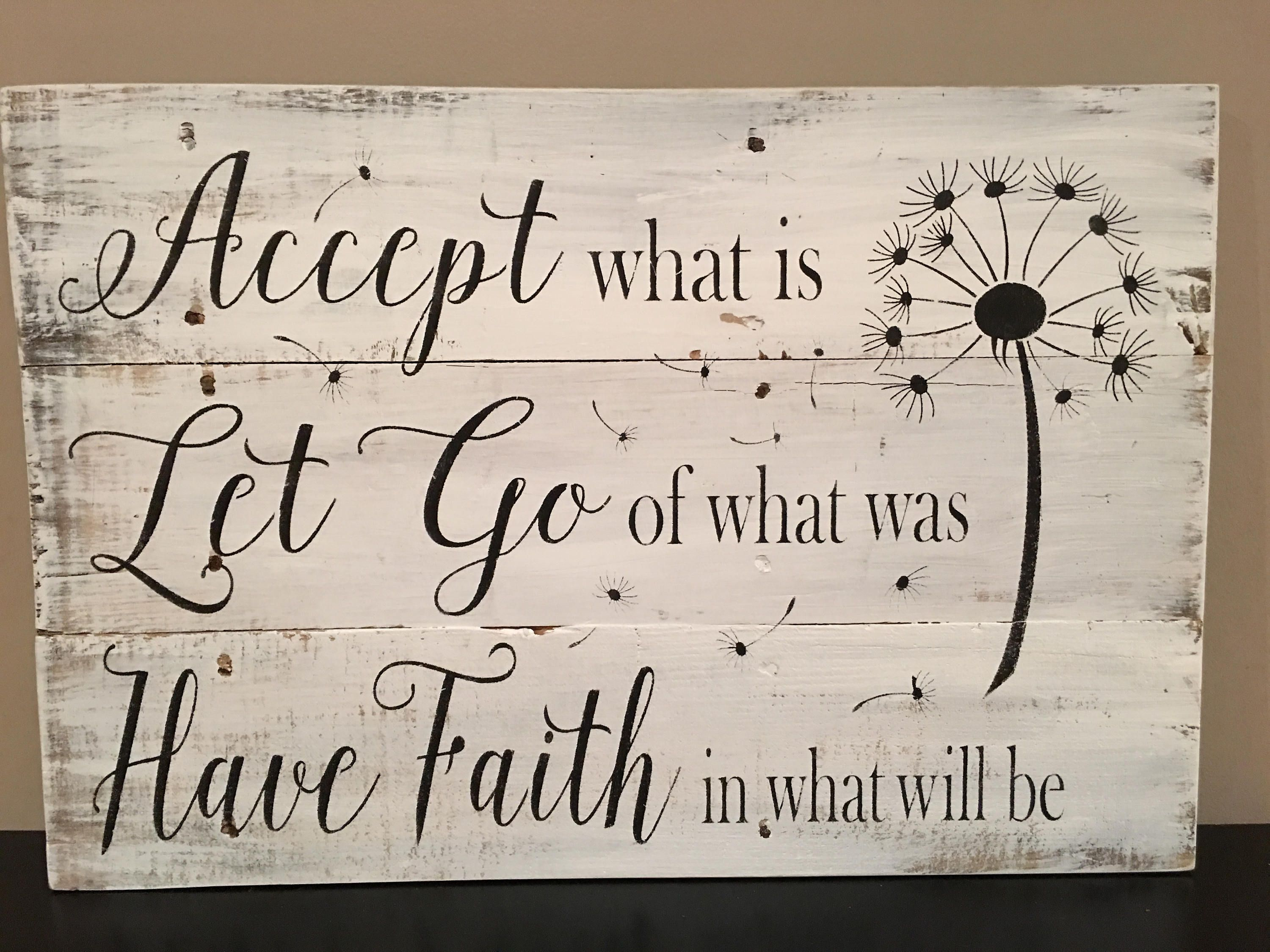 Accept what is sign is shown on reclaimed pallet boards with a white