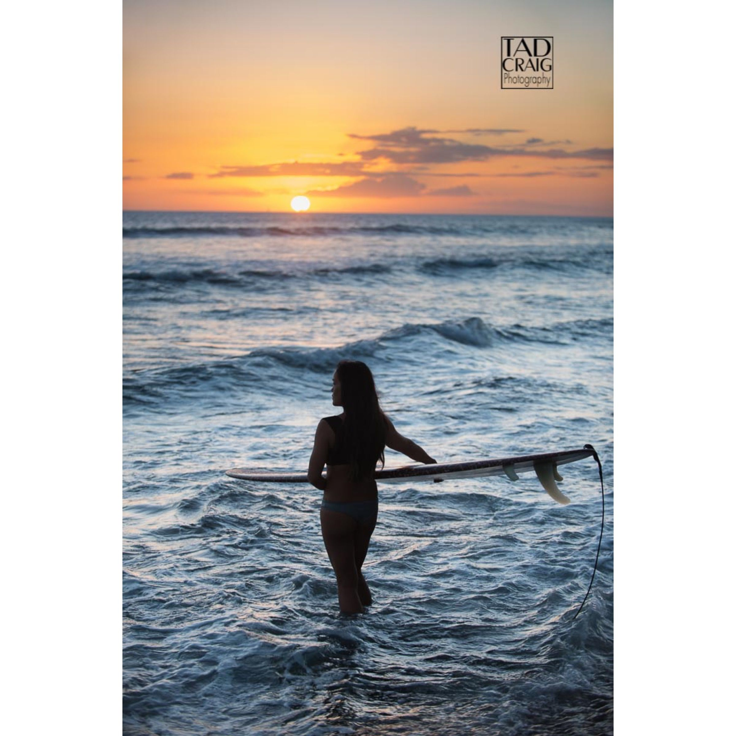 Silhouetted surfer girl about to catch waves at sunset in west Maui.  Photo by www.TadCraigPhotography.com