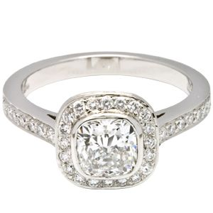 A striking cushion cut solitaire ring with a 1.01ct certified diamond and a uniform halo of smaller stones surrounding the main diamond. The ring is completed by a platinum band with elegant diamond shoulders.
