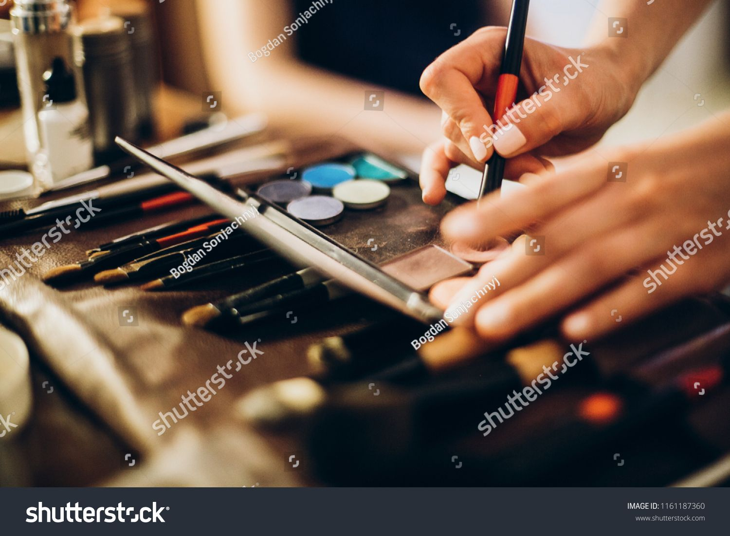 hands holding brush and eyeshadow palette. makeup artist