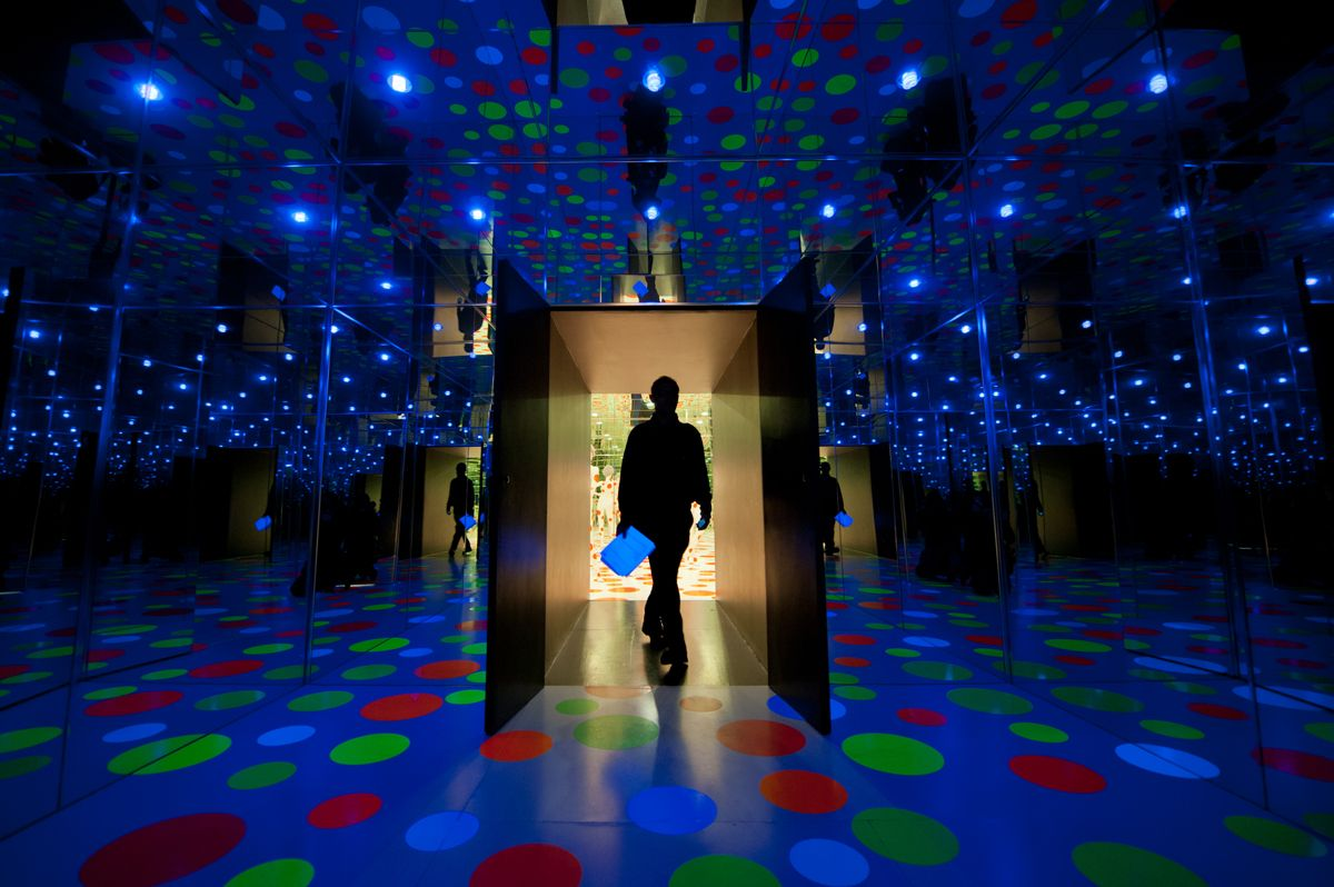 """Asher Reny-Toledo, visiting from New York City, walks through a door from Yayoi Kusama's """"Repetitive Vision"""" installation into her """"Infinity Dots Mirrored Room"""" installation at the Mattress Factory on the North Side on Wednesday, January 2, 2013. The room sized works, assembled in 1996, have walls and ceilings made of mirrors and Formica floors with polka dot decals that reflect in the mirrors around the viewer. (Stephanie Strasburg 