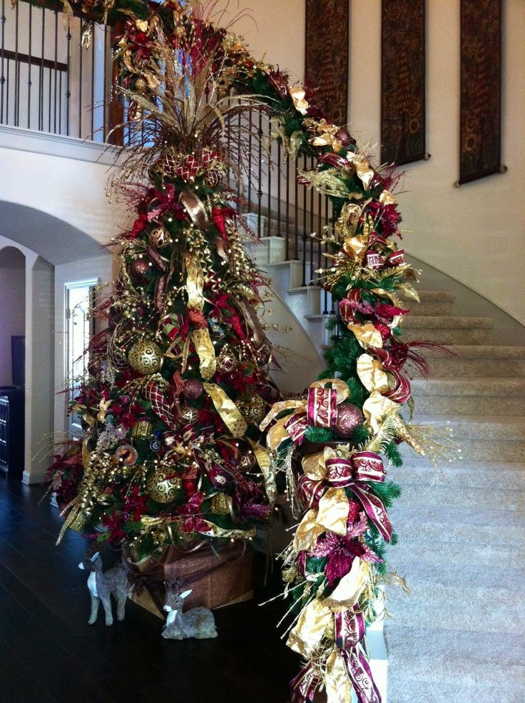 Burgundy And Gold Christmas Tree Against The Staircase