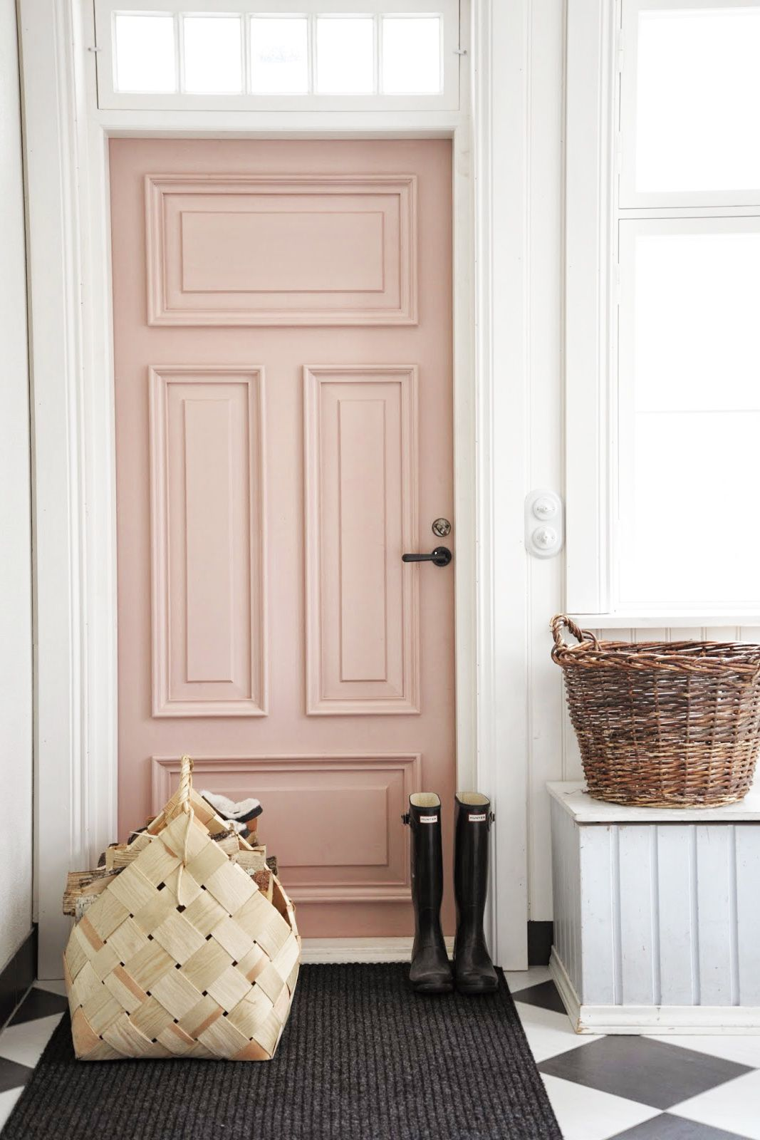 Rose door inside home with tiled black-and-white floors