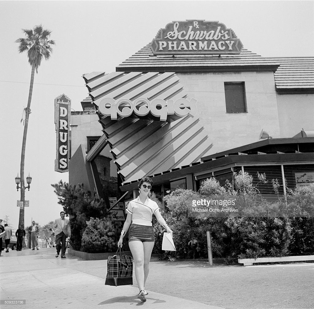A Woman Walks Outside Googies Coffee Shop And Schwab S Pharmacy In Googie Architecture Googie Space Age Modern