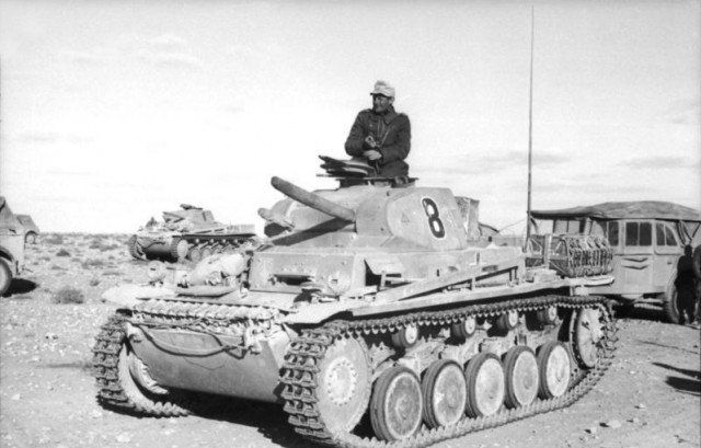 Nordafrika, Panzer II, Kraftfahrzeuge. The commander of a Panzer Mk II stands in his turret, another Mk II can be seen in the background.