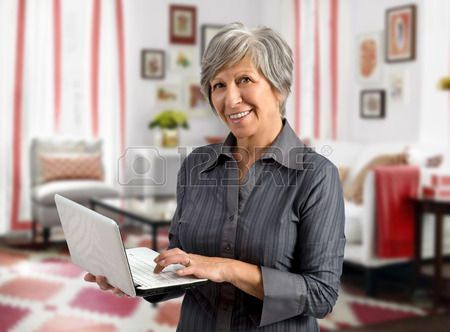 Senior woman using her handheld laptop as she stands in the living room of her house surfing the int Stock Photo