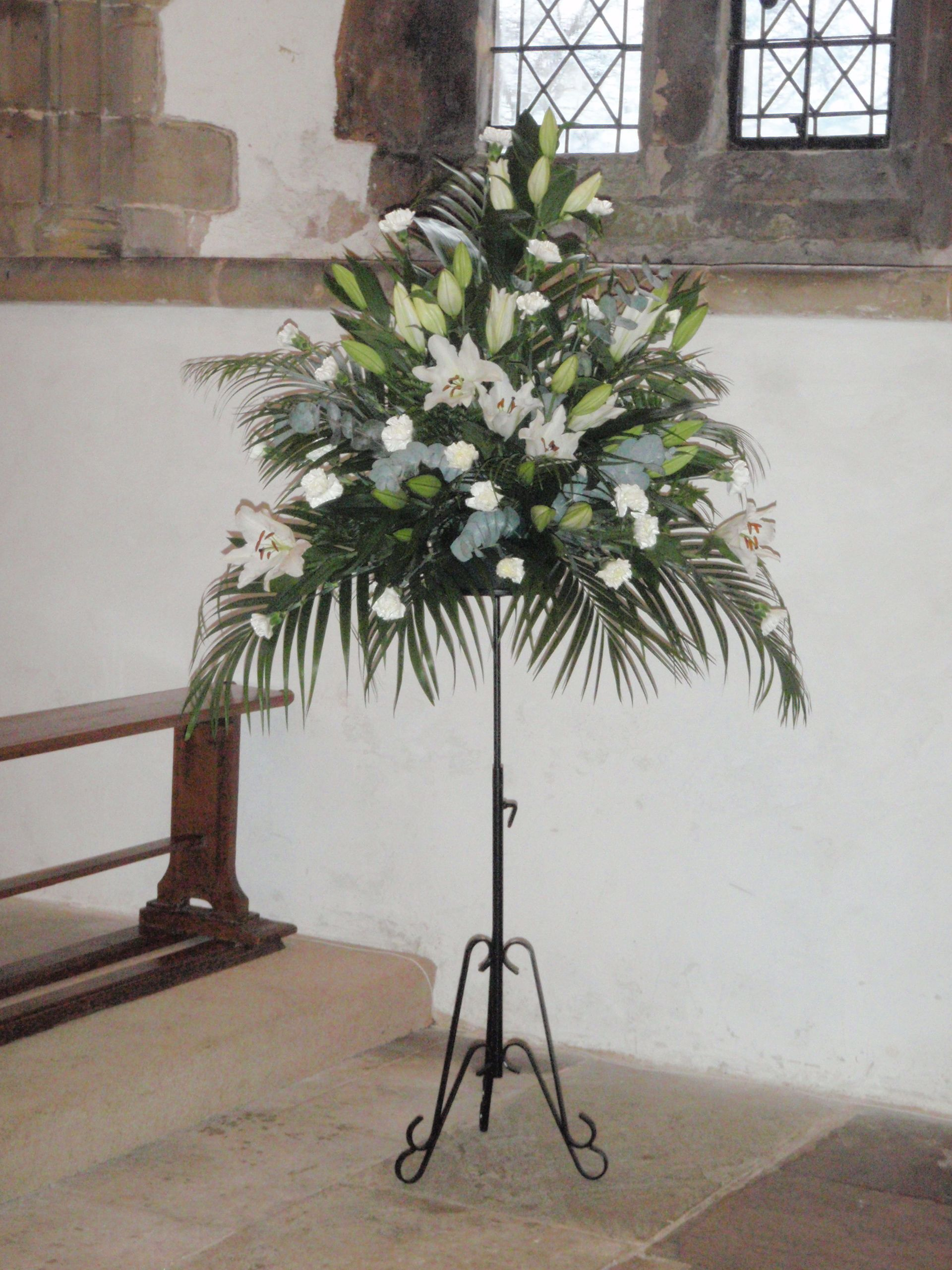 Church Pedestal With White Lilies Carnations Palm Leaves And Eucalyptus