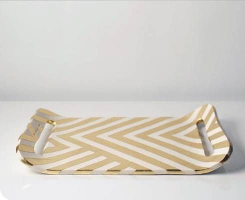 The beautiful Zag earthenware tray is hand-made in Chicago by Susan Dwyer of Up in the Air Somewhere. A gold leaf is applied to the ceramic tray in a graphic chevron-inspired pattern. The gold-leaf is sealed but should only be gently sponge-washed and the tray is for decorative use only.-8 x 10 inches