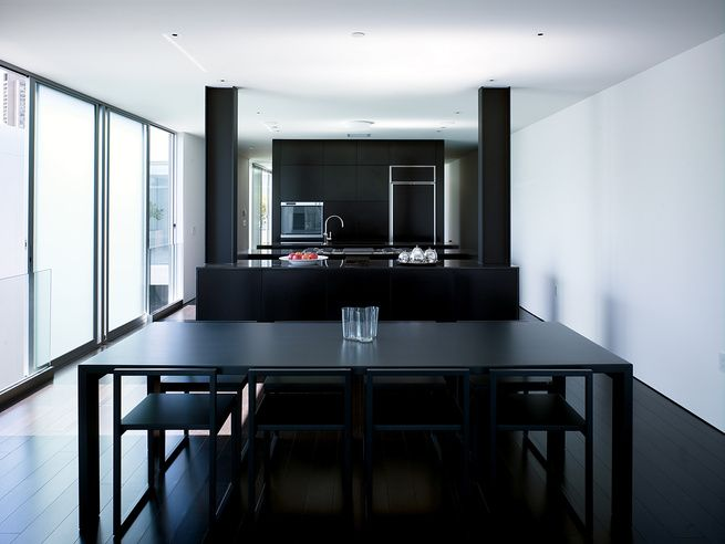 "The ""daytime"" living quarters in the penthouse are dark, from the floor to the furnishings. The dining table is by Jasper Morrison for Cappellini (with an Aalto vase by Iittala on top). The chairs are by Ag Fronzoni also for Cappellini.  Photo by: Dwight Eschliman"