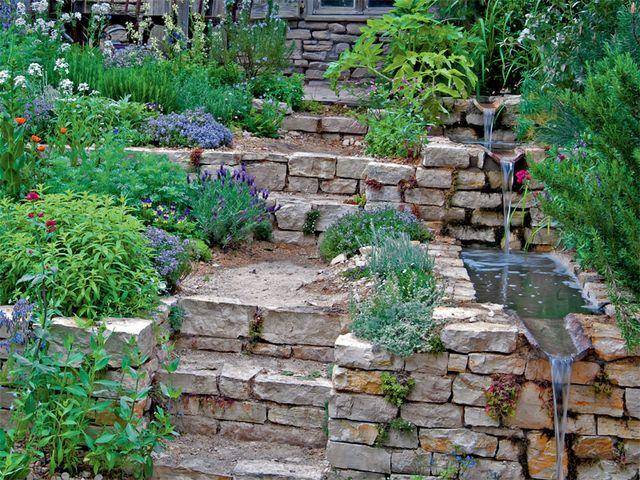 Wasserlauf am Gartenhang mit Natursteinen und Treppe im Garten ...
