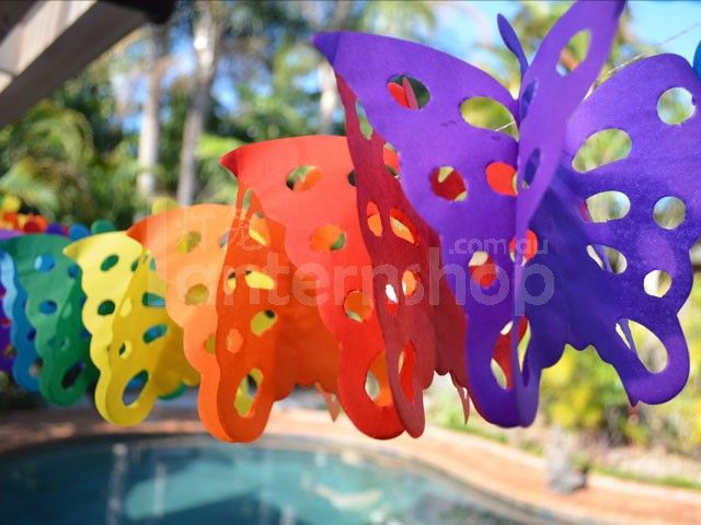 Paper Garlands Decorating a Christmas pool party with hanging, butterfly themed paper garlands.