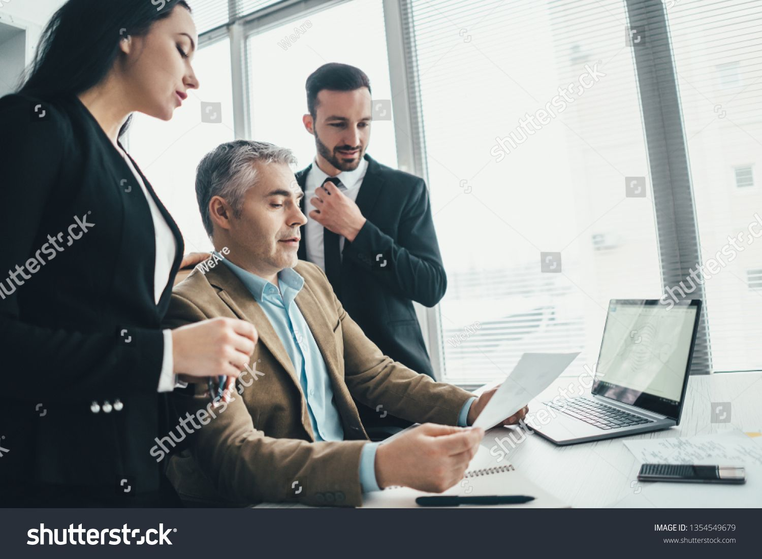 The three business people discussing near the laptop