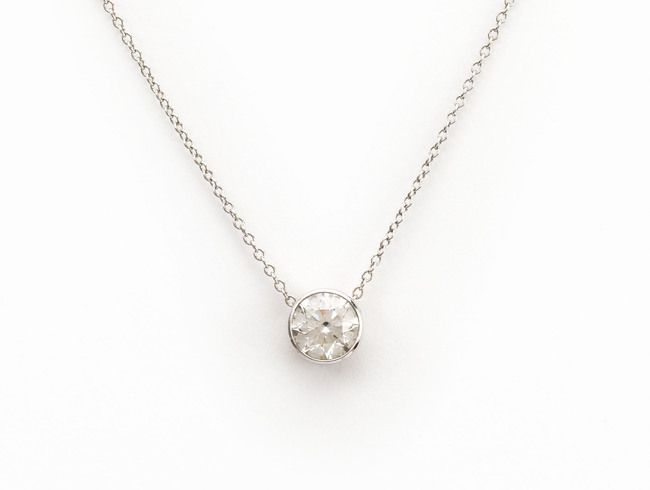 A diamond pendant, mounted in platinum, with a platinum chain running through the rub-over setting, set with a 0.90ct G VS2 round brilliant-cut diamond. Accompanied by a GIA certificate. Please contact us on suzanne@moira-jewels.com with any questions
