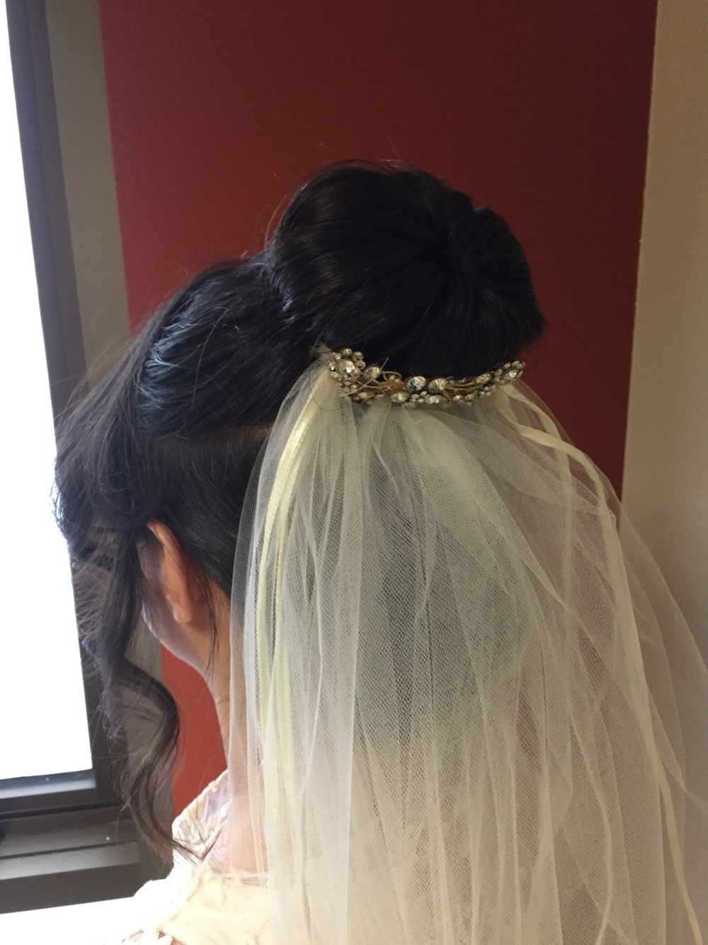 An upstyle bun curled tendrils at the front and veil placed in the back