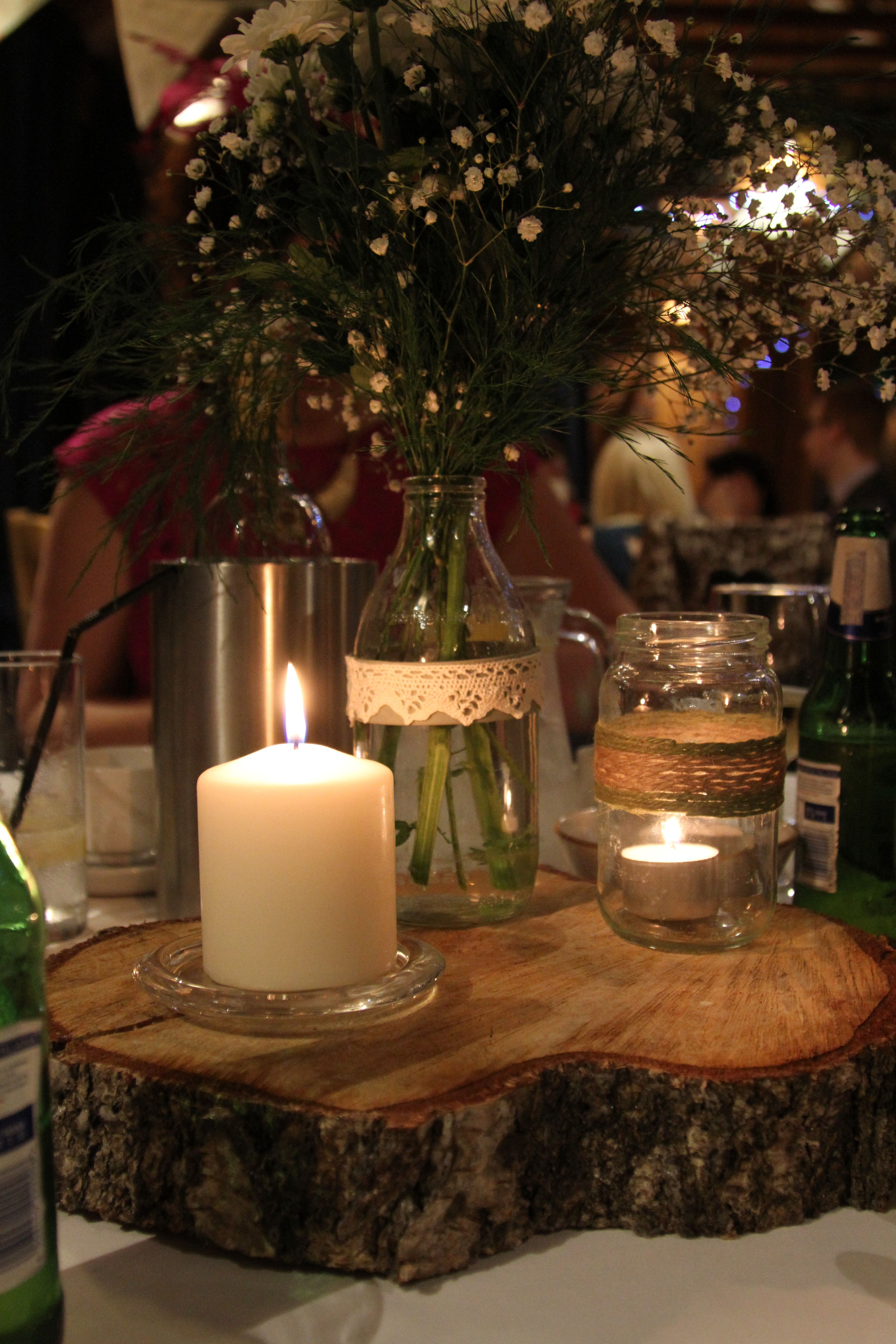 Log, candles, mason jars, flowers make a great centre
