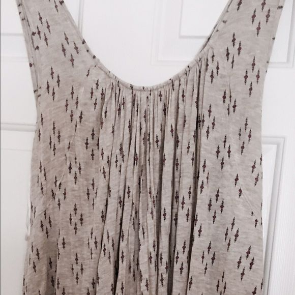 Adorable boho sleeveless top from Free People! Adorable, flowing, draped sleeveless top from Free People! Heather gray with burgundy and navy little designs all over - open tie back, super flattering - the back drapes with extra material so when you lift your arms it's almost like a bat wing, but with your arm down it looks like a regular draped front/back. Because of the cut it would look fantastic on a size m-2x! Paid 88$ at FP. Free People Tops Tank Tops