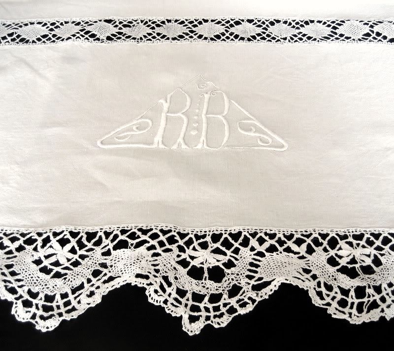 Triangular monogram RB embroidered on a pure linen sheet between deep bands of handmade bobbin lace from Le Puy en Velay. Sold by chatelaine-chic.