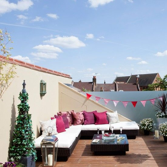 Summery roof terrace  In a city house or flat a rooftop garden is a great solution, especially for outdoor entertaining in summer months. Neat modular furniture with plump white and pink cushions looks festive paired with cheery bunting, while planters and storm lanterns provide a grown-up finish.