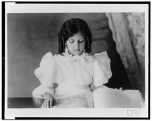 African American girl, half-length portrait, looking at open book LCCN99472111.tif