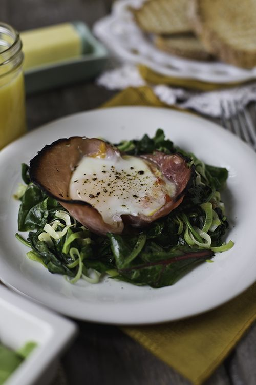 baked eggs in ham cups, served on dressed, sauteed greens.
