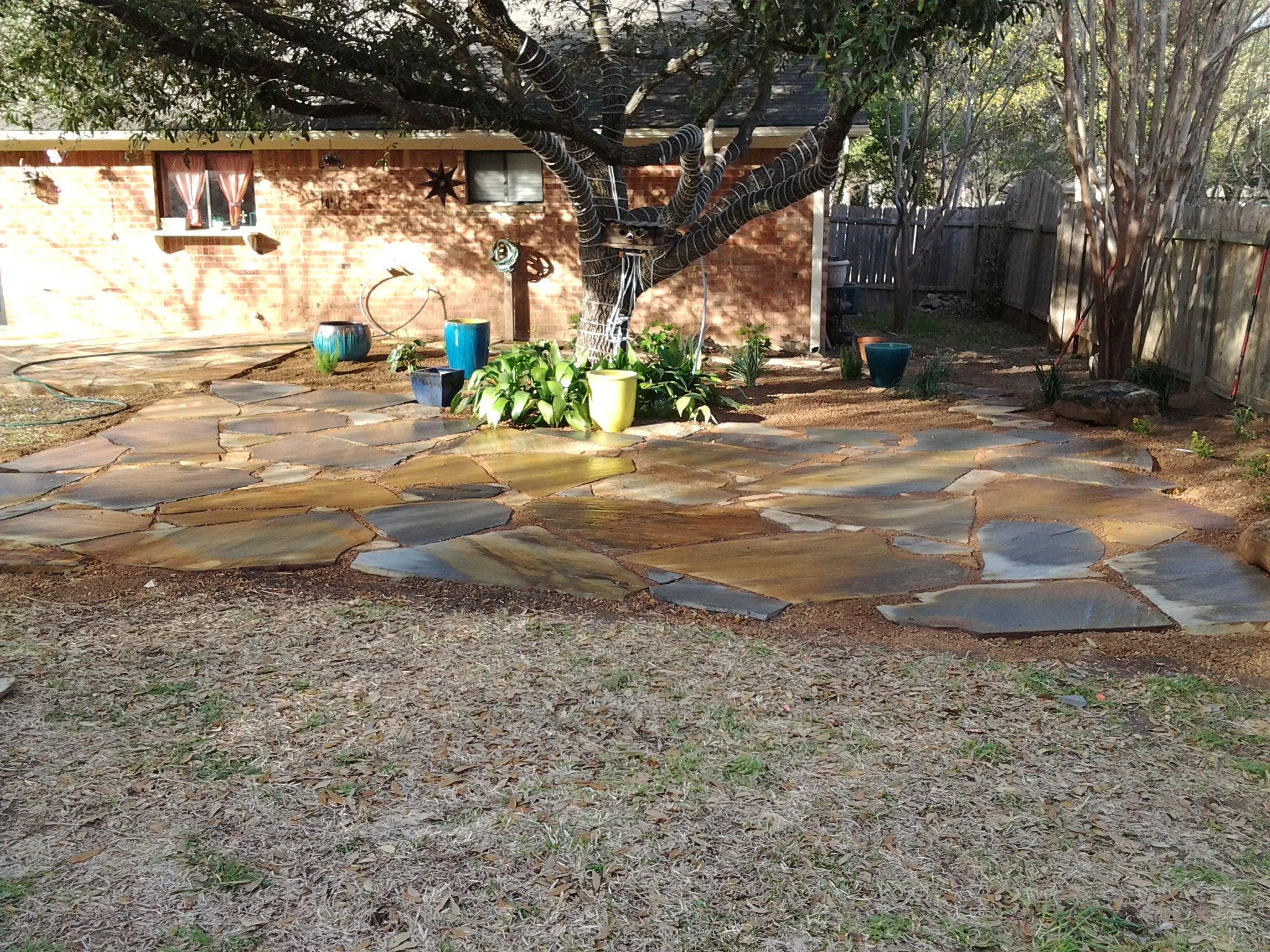 Flagstone patio set in de posed granite with containers for