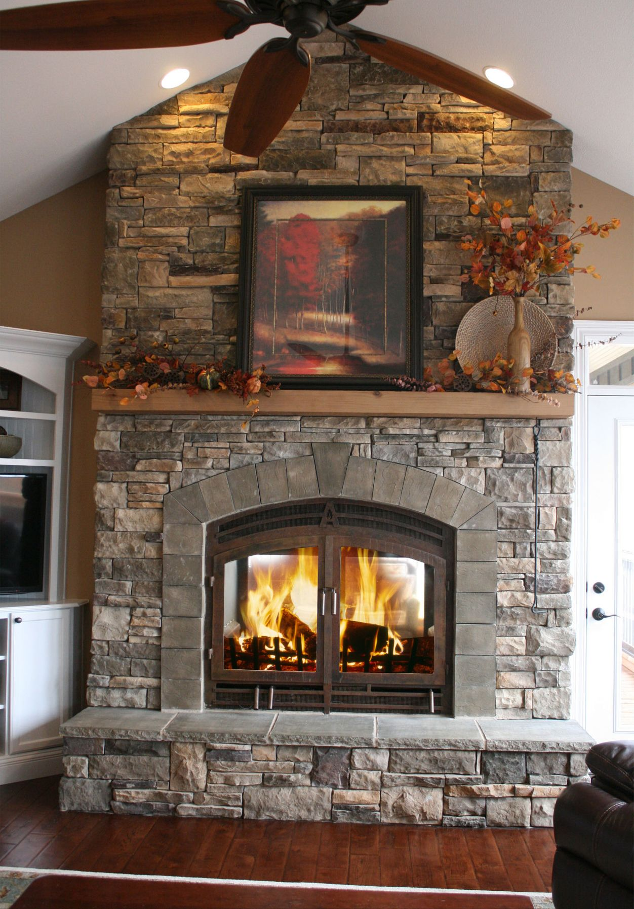 FloortoCeiling stone fireplace with fullwidth wood mantel