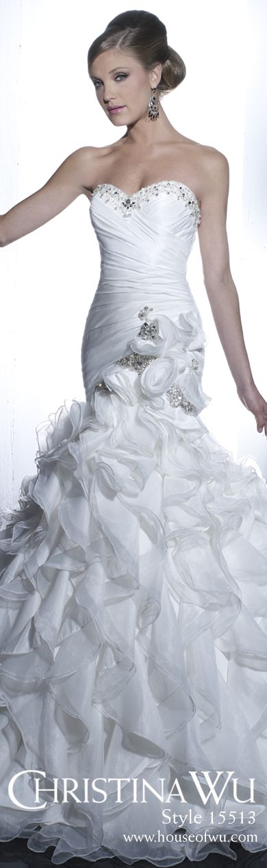 This strapless Christina Wu wedding dress features a sweetheart neckline with crystal and pearl embellishment, a pleated bodice with floral accent and trumpet skirt of ruffles with train.