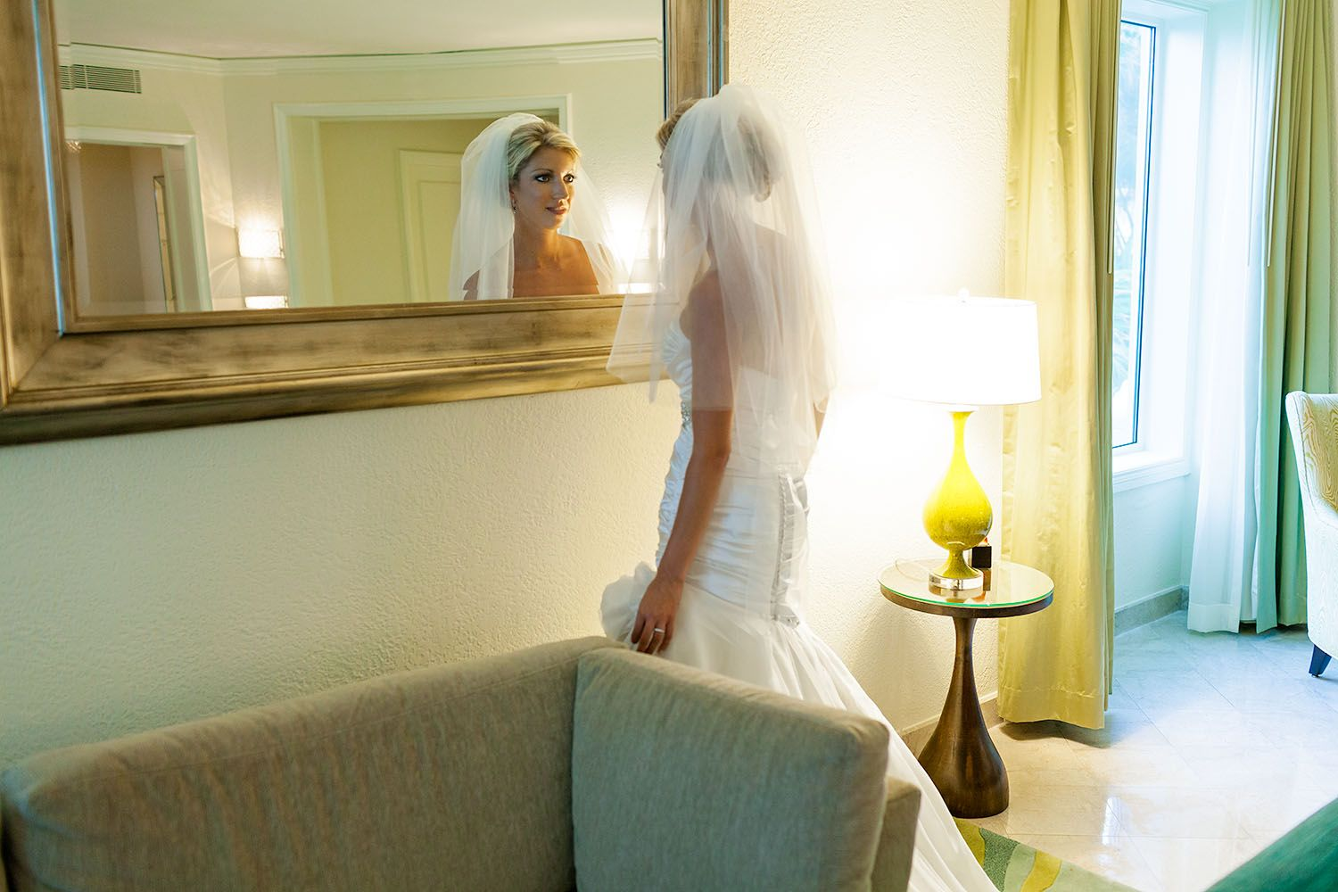Bride mesmerized with her reflection in the mirror of the bridal suite on her wedding day at the island wedding destination Ritz-Carlton, Puerto Rico #bride #gettingready #destinationweddingphotographerpuertorico
