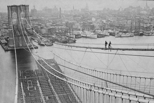 "cinoh: "" Two men standing on a catwalk surveying the construction of the Brooklyn Bridge, with Manhattan in the background.CreditMuseum of the City of New York, via Getty Images """