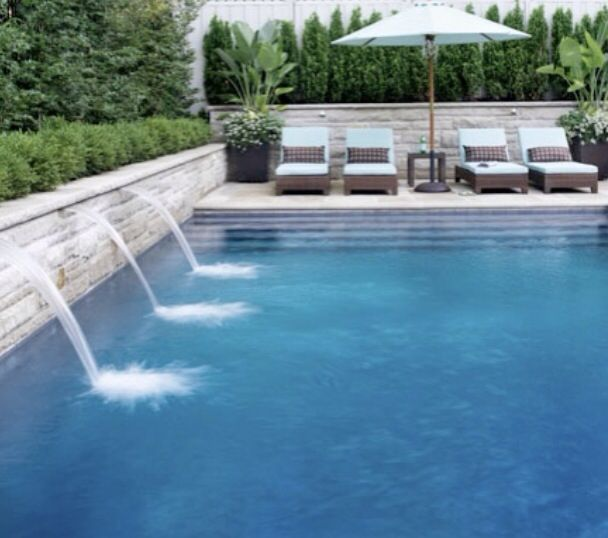 Handsome Pool With Limestone Wall Water Spouts Privacy Hedges