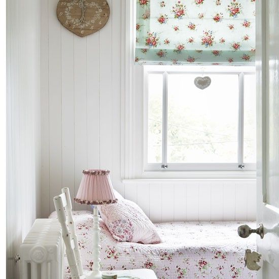 Girly guest bedroom  Similar-sized florals in various colours, on a plain background, create a simple, feminine look. Wood panelling adds classic country style.