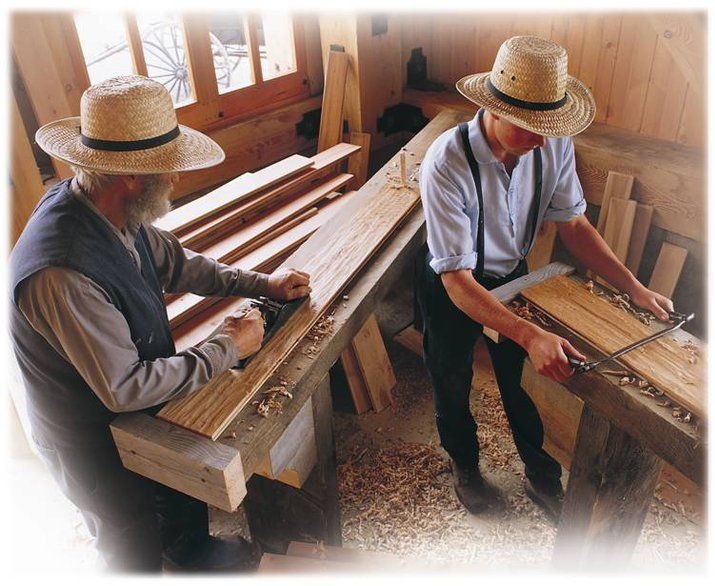 An older Amish man, and a younger one, work on making ...