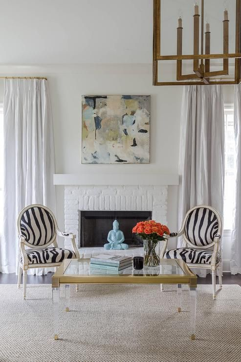 stunning living room features a pair of french zebra chairs and a lucite and brass coffee white brick