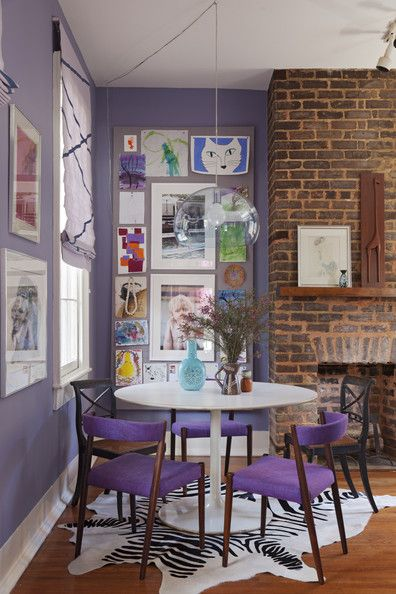 April 2013 Issue: A gallery wall of art beside a brick fireplace.