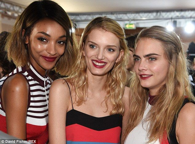 Glowing glamour: Jourdan Dunn, Lily Donaldson and Cara Delevingne shared a moment before taking to the runway
