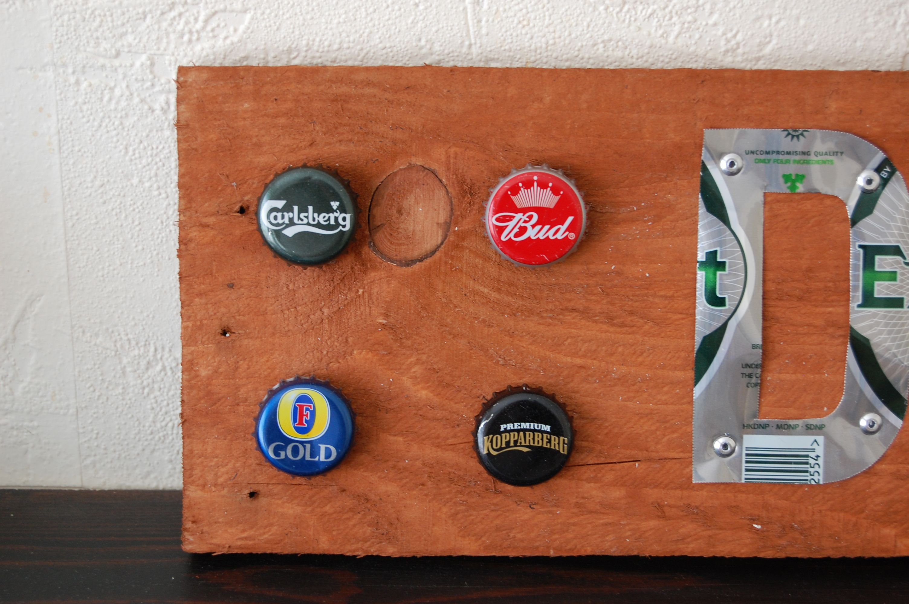 I made this with hand cut letters from John Smith and Carlsberg Export aluminium drink cans. I've hand riveted them on to a bit of used pallet wood stained medium oak. To the ends I've hand glued various metal bottle tops. Perfect for weddings, parties, BBQ's or any function, non alcoholic versions can be made.