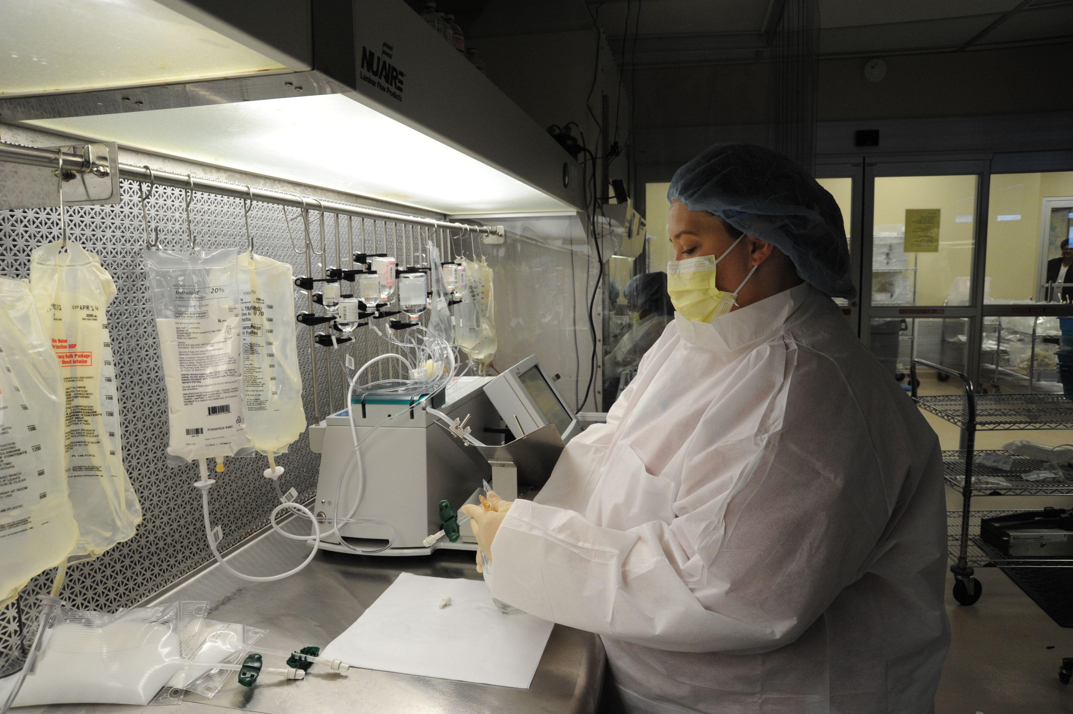 A pharmacy technician mixes and prepares medicine for