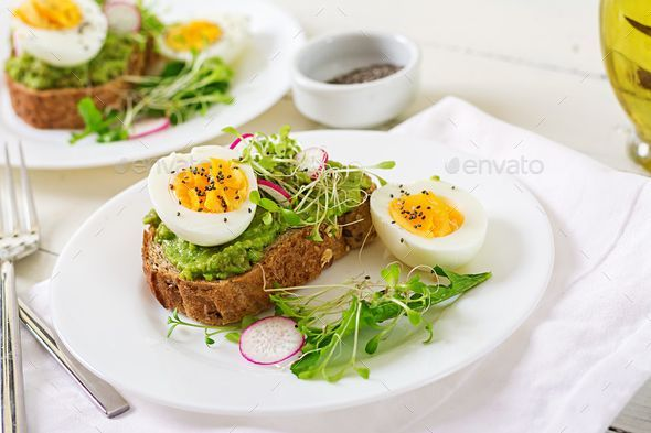 food. Breakfast. Avocado egg sandwich with whole grain bread on white wooden background. by Timolina. Healthy food. Breakfast. Avocado egg sandwich with whole grain bread on white wooden background.Healthy food. Breakfast. Avocado egg sandwich with whole grain bread on white wooden background. by Timolina. Healthy food. Breakfast. Avocado egg sandwi...
