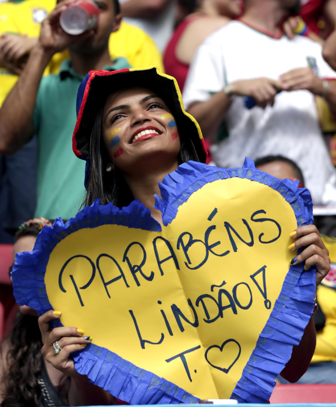 World Cup Crush: Photogenic fans of the World Cup - Day 8 - A Colombian supporter holds a sign saying 'Congratulations Handsome' before the group C World Cup soccer match between Colombia and Ivory Coast at the Estadio Nacional in Brasilia, Brazil, Thursday, June 19, 2014.