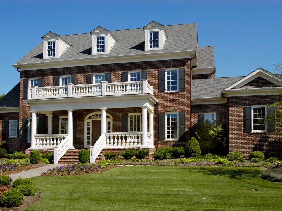 Black Shutters And A White Front Porch Balcony Are Classic Accents To This Colonial Brick