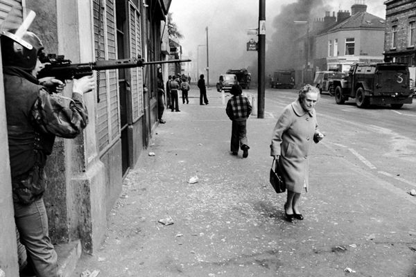 N.IRELAND. Belfast. Catholic West Belfast, Falls Road. Hijacked vehicle burns in the background marking the anniversary of the British Policy of internment without trial. 1978.